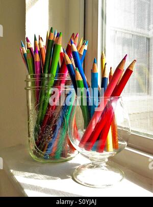 An assortment of colored pencils in glass containers sits on a sunny window sill - Stock Photo