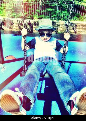 A young boy wearing hat and sunglasses plays on s swing in the park. - Stock Photo
