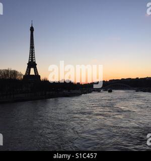 Eiffel Tower in Paris on a winter sunset from a bridge crossing river Seine - Stock Photo