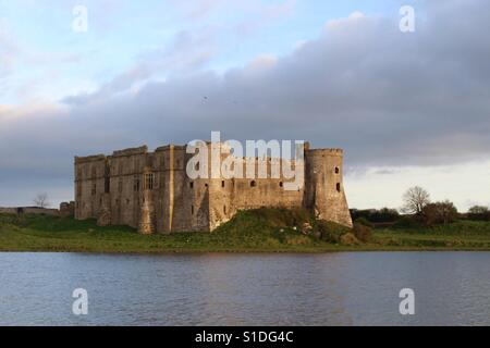 Carew Castle and Mill at sunset in Carew, Pembrokeshire, UK. Credit: Ollie Cole. - Stock Photo