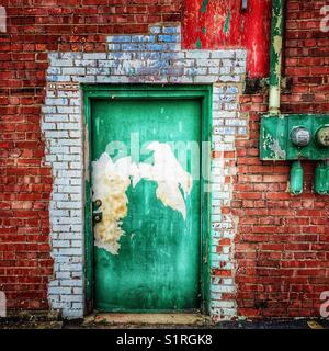 Weathered green door on old brick building - Stock Photo