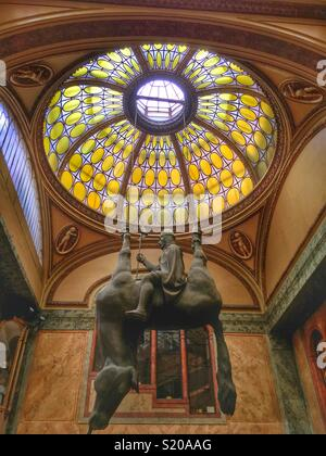 Statue of King Wenceslas Riding an Upside-Down Dead Horse in Prague, Czechia: A mocking tribute to the past and modern leadership of Prague. Art Nouveau Lucerna Palace. By David Cerny. - Stock Photo