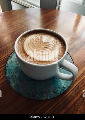Gourmet coffee latte cappuccino drink in large white mug with decorative milk foam cap on softly lit wooden table with green marble inlay with window in the background - Stock Photo