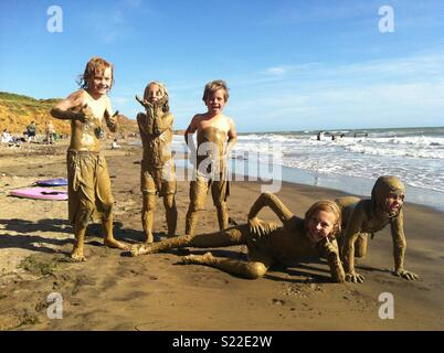 Sandy children posing on the beach after covering themselves in mud, Compton, Isle of Wight - group of friends having fun by the sea - Stock Photo