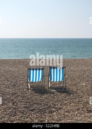 Two blue and white striped deckchairs on Brighton beach, UK. - Stock Photo