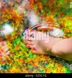 Children's feet in a kiddy pool full of Orbeez gel beads - Stock Photo