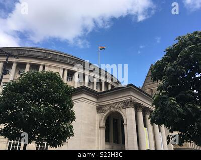 Gay flag flying at Manchester library - Stock Photo
