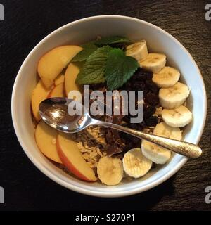 Mouthwatering Muesli. Cereals, bananas, apples, raisins and chocolate in a white ceramic bowl and spoon for breakfast, Germany, Europe - Stock Photo