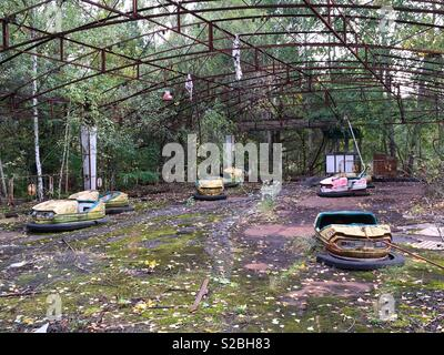 Old and abandoned bumper cars in the town of Pripyat near Chernobyl - Stock Photo