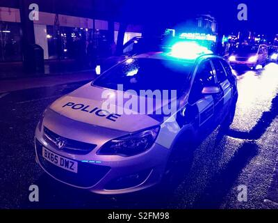 Police car parked on a city street at night with blue lights flashing - Stock Photo