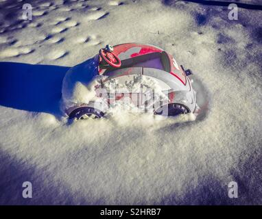 Pink car covered with snow casting a shadow - Stock Photo