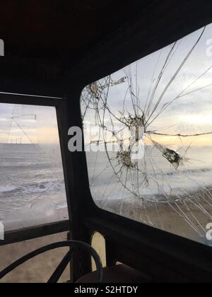 Beach viewed through a broken window of a vehicle. Caister-on-Sea, Norfolk, UK. - Stock Photo