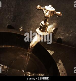 Cold tap running water in a bathroom, England, United Kingdom - Stock Photo