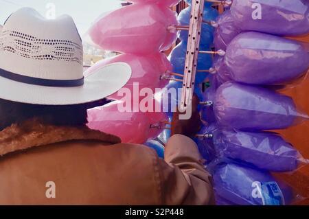 A cotton candy vendor walks into downtown San Miguel de Allende, Mexico. - Stock Photo
