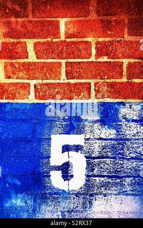 Number five on blue and white painted brick wall background with unpainted brickwork above - Stock Photo