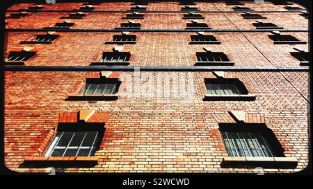 Windows on a red-brick warehouse building in Bristol, England - Stock Photo