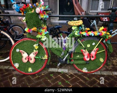 A beautifully decorated nature themed bicycle featuring fake grass, butterflies and flowers in Amsterdam, The Netherlands - Stock Photo