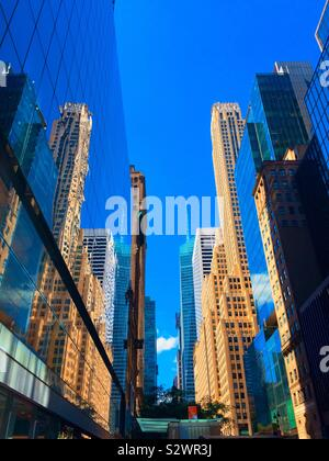 Skyscrapers and their reflections in a canyon of buildings looking west on 42nd St., Midtown Manhattan, NYC, USA - Stock Photo
