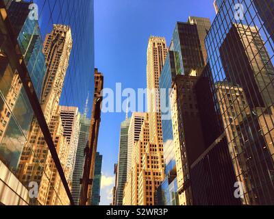 Skyscrapers and their reflections in the glass the side of 300 Madison Ave. looking west on 42nd St., Midtown Manhattan, NYC, USA - Stock Photo