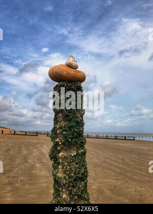 Pebble tower on a post at the beach - Stock Photo