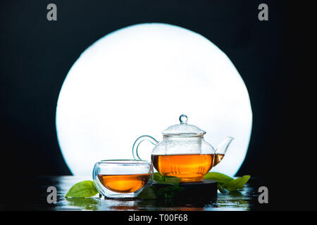 Asian tea ceremony still life header with a full moon. Glass tea bowl and teapot against a shining circle. - Stock Photo