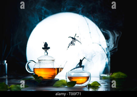 Conceptual tea photography with ninja silhouettes on tea cups. Creative hot drink header with full Moon and copy space - Stock Photo