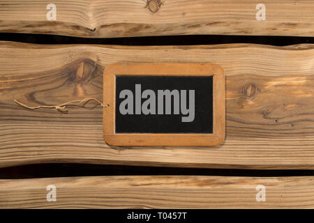 Old authentic chalkboard/blackboard on rustic wooden planks. Space for copy/text, signage, banner. - Stock Photo