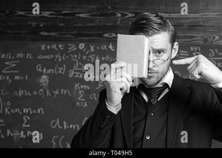 Handsome student in suit covering his face with book while pointing at it with other hand. Closeup portrait of young blond aristocrat with stylish - Stock Photo