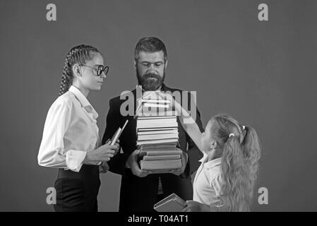 Teacher man and girls hold book pile at school. School time of sisters and father in library. Education in knowledge day. Literature lesson and - Stock Photo