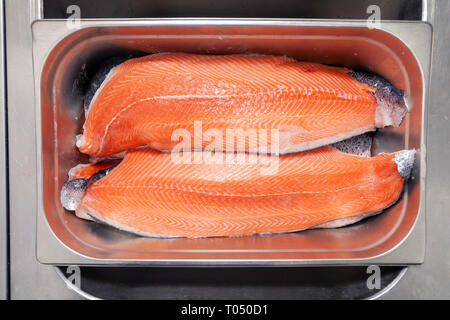 Closeup fresh norwegian salmon fillet fish in metal bowl tray on professional restaurant kitchen. Textured background. Concept carving fish, cooking s - Stock Photo