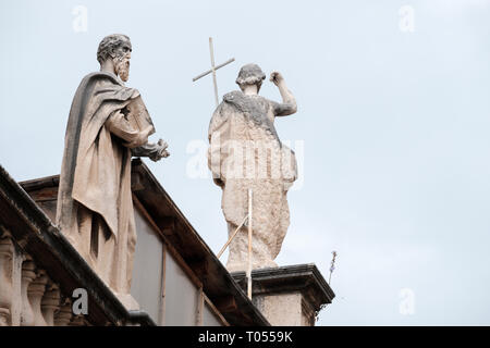 Two ancient statues of holy men on top of one of the buildings in Dubrovnik old town, Croatia - Stock Photo