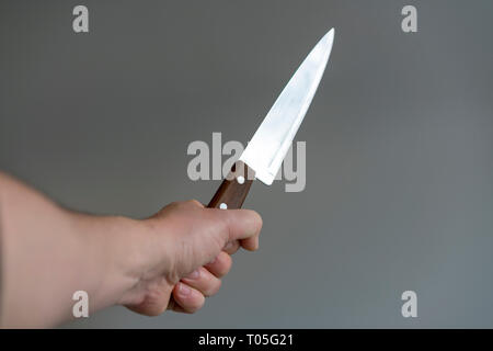 Man's hand with a knife on gray background. Concept of violence. - Stock Photo
