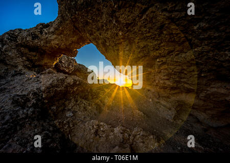 Sunset and mountain landscape view from eroded stone arch know as Ventana del nublo or La Agujereada. One of the higest places in Gran Canaria Island. - Stock Photo