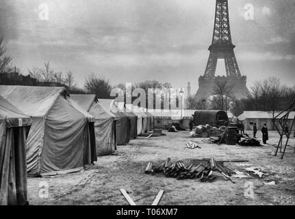 Paris, France. The American Red Cross Enlisted Men's Hotel #13, at Champ de Mars, Paris, in the course of construction. Made entirely out of salvaged tents, there are accomodations for 1,400 men. A fully equipped canteen and recreation hut go to make this hostely complete. The work was started on February, 18th and finished in nine days. It was necessary for the Red Cross to provide sleeping places quickly, for the men, passing through Paris, were coming in great crowds. In the shadow of the Eiffel Tower, it is indeed an ideal site for the purpose. February, 1919 - Stock Photo