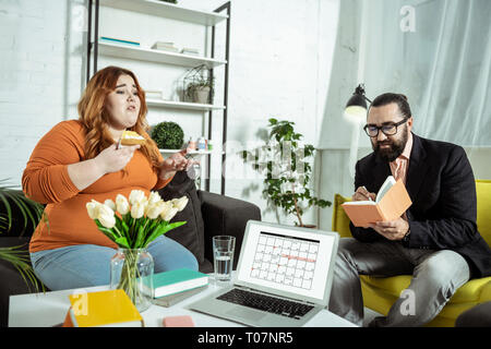 Serious bearded man making notes during consultation - Stock Photo