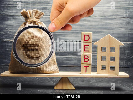 Money bag and wooden blocks with the word Debt and a miniature house on the scales. Payment of debt for real estate. Pay off the mortgage loan. Risks  - Stock Photo