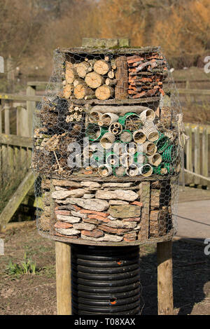 Insect or bug hotel built using a variety of materials including dry stone walling, logs and bundles of sticks at the Wildfowl and Wetland Trust, Slim - Stock Photo