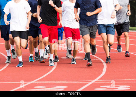 High school boys running in a large group on a red track during cross country practice. - Stock Photo