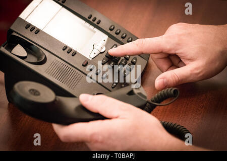 Finger dialing phone call on touch tone telephone. - Stock Photo