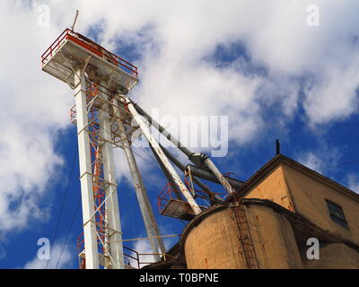 grain silo with elevator against blue sky - Stock Photo