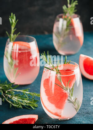 infused detox water or alcoholic or non-alcoholic cocktail with grapefruit and rosemary in glass on green and black cement background. healthy eating or holyday drink concept, copy space for text - Stock Photo