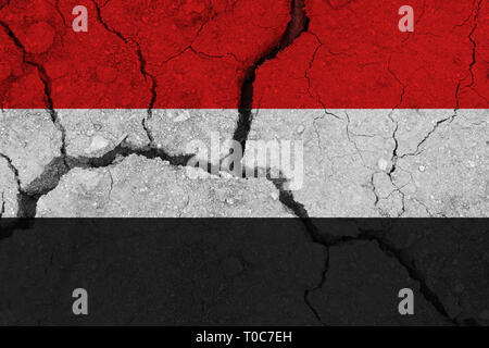 Yemen flag on the cracked earth. National flag of Yemen. Earthquake or drought concept - Stock Photo