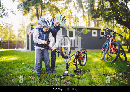 Two children, older boys and younger brother learning repair bike. Two guys siblings in helmets and single clothes use pump tool and pump air into - Stock Photo