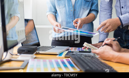 graphic designer team working on web design using color swatches editing artwork using tablet and a stylus At Desks In Busy Creative Office - Stock Photo