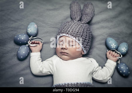 Portrait of a cute little baby boy wearing bunny costume and holding decorative eggs in hands, happy Easter holiday - Stock Photo