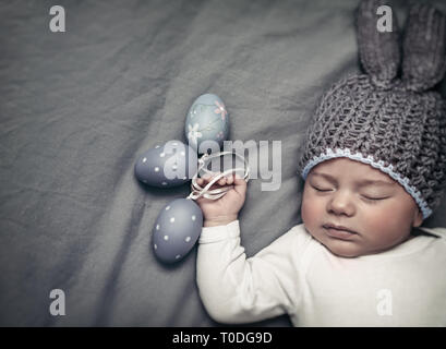 Closeup portrait of a cute little baby boy wearing bunny costume and sleeping with decorative eggs in hands on gray background, photo with copy space, - Stock Photo