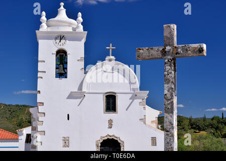 Idyllic white washed church with medieval cross in front of baby blue sunny  sky - Stock Photo