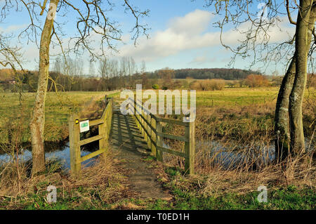 A footbridge over a tributary of the river Kennet near Axford, Wiltshire. - Stock Photo