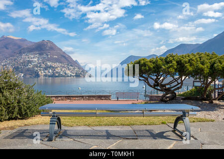 The bench at the Lake Lugano and Alps mountains in Ticino canton of Switzerland - Stock Photo