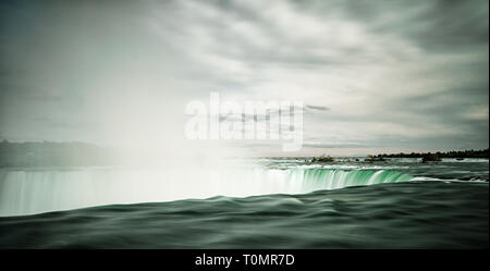 view of the tumbling waters of Horseshoe Falls at Niagara Falls with water steam rising from the cascading waters - Stock Photo